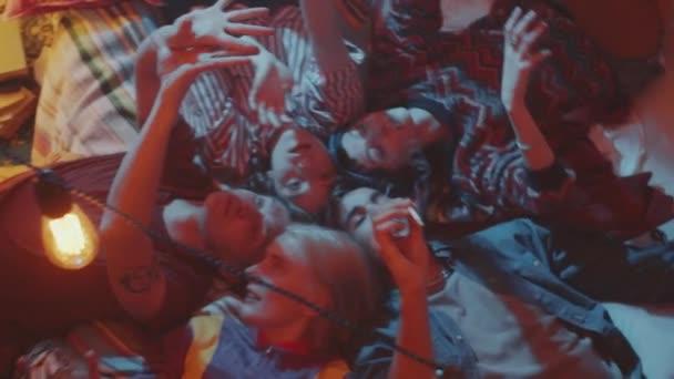 Aufnahme einer Gruppe junger Freunde, die Kopf an Kopf auf dem Bett liegen, Zigaretten rauchen und am Aschenbecher vorbeigehen, während sie sich zu Hause auf einer Retro-Party entspannen