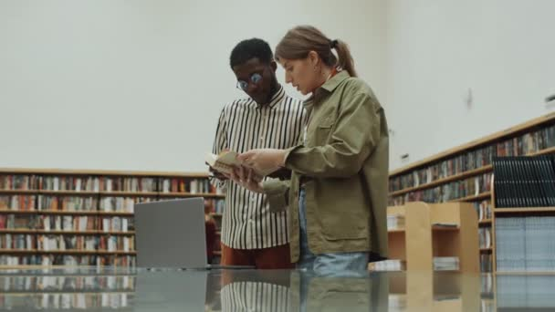 Young multiethnic man and woman standing in library, using laptop, reading book and speaking