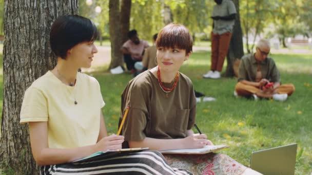 Portrét dvou mladých vysokoškolaček sedících s propiskami a podložkami na trávě v parku, mluvících a dívajících se na kameru a usmívajících se