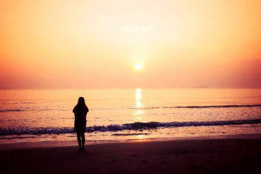 silhouette of woman alone and wave on the beach