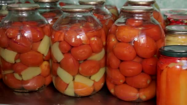 Tinned tomatoes and cucumbers in glass jars on stillage