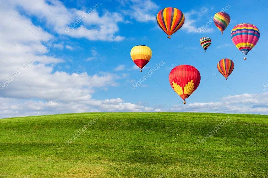 Colourful hot air balloons flying over green field and blue sky