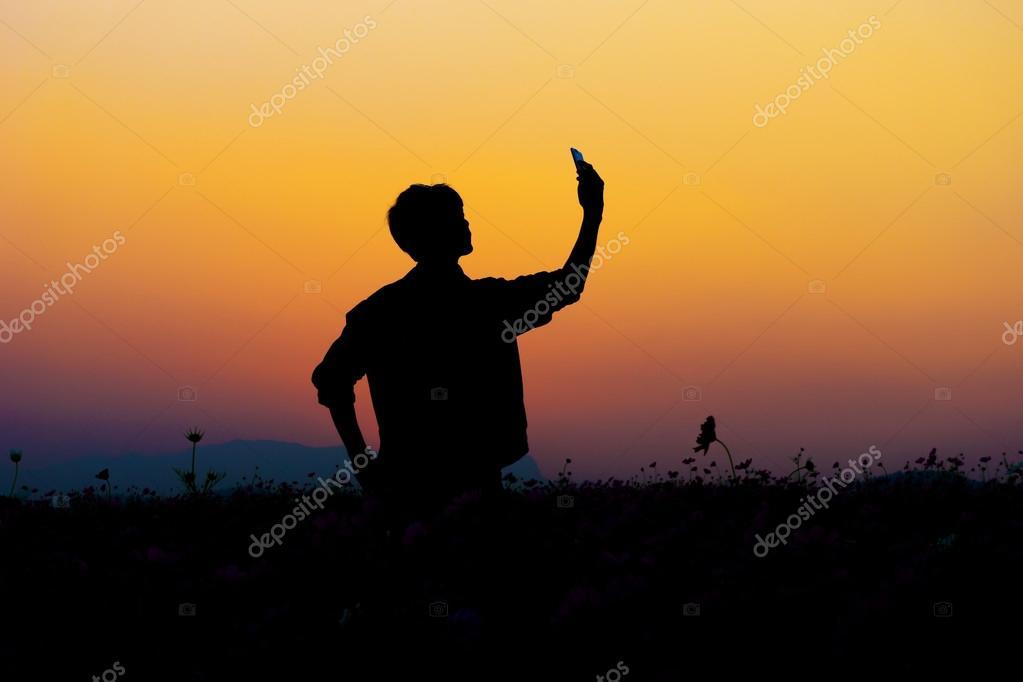 Silhouette of man selfie. Silhouette of man posing at sunset sky