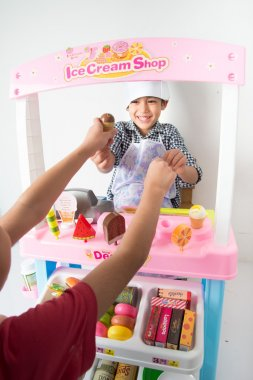 Little boy playing pretend as a saler in icecream shop