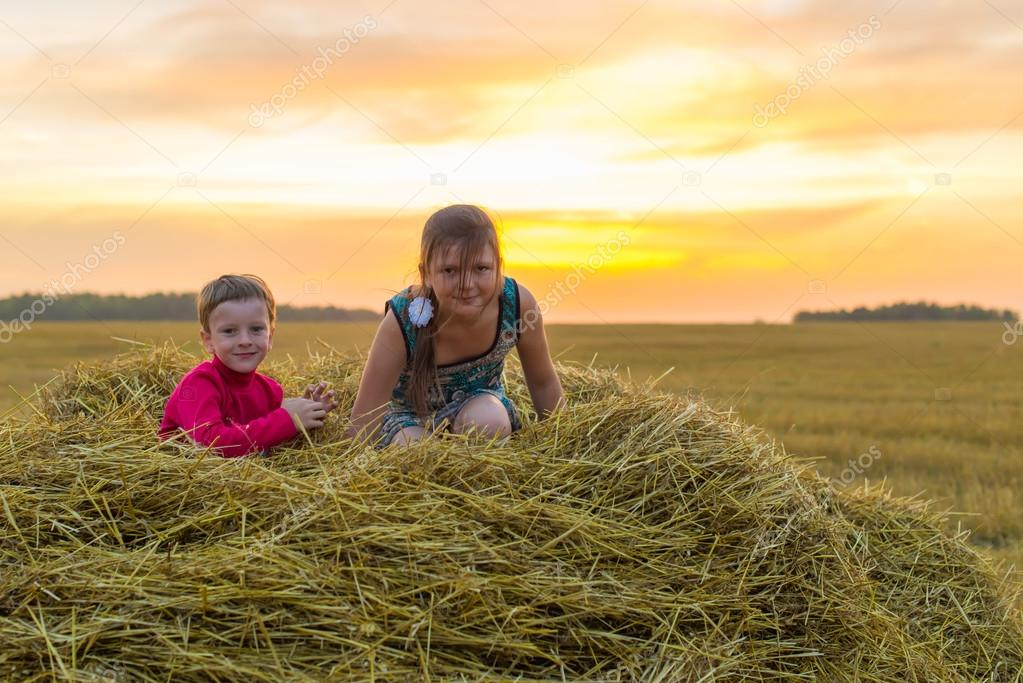 Boy and girl standing on a stack of straw