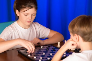 Children boy and girl playing a board game called Checkers