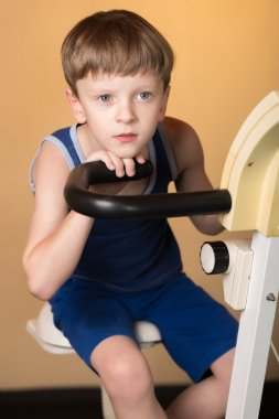 The child is trained on a stationary bike . Healthy lifestyle.