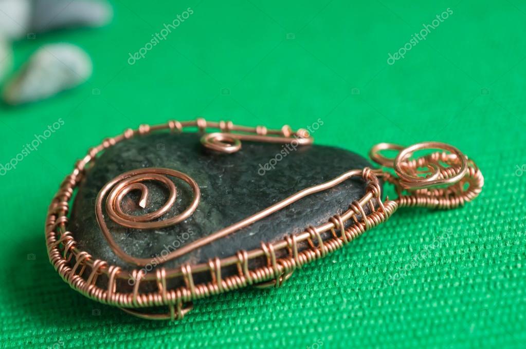 Schmuckanhänger aus dem Stein von einem Kupferdraht geflochten ...