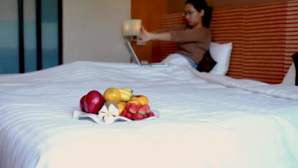 Ovoce v podnosu na posteli v luxusním hotelovém pokoji před asijské ženy traveler stretch a pomocí notebooku.