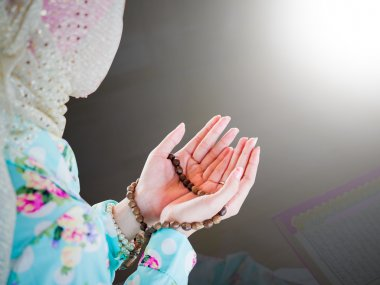 young muslim woman praying for Allah