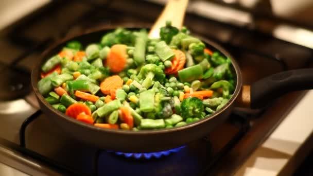 Frau mischt gefrorenes Gemüse