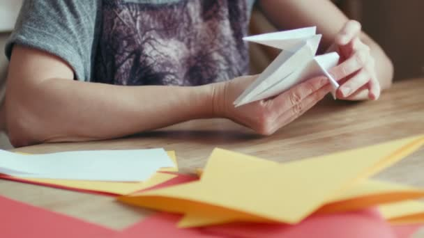 hands making origami crane