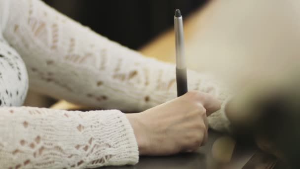 Hands of a woman working with drawing tablet