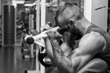 The athlete does bench biceps on the simulator in the gym. Hand muscle training on the simulator. Tense muscles of hands under load. Photos for sporting magazines, posters and websites.