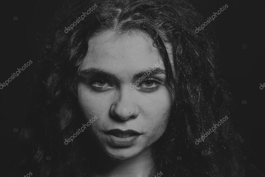 Black and white portrait photo of a young girl on a dark background inscrutability and concentration in view of the girl clear features beautiful young