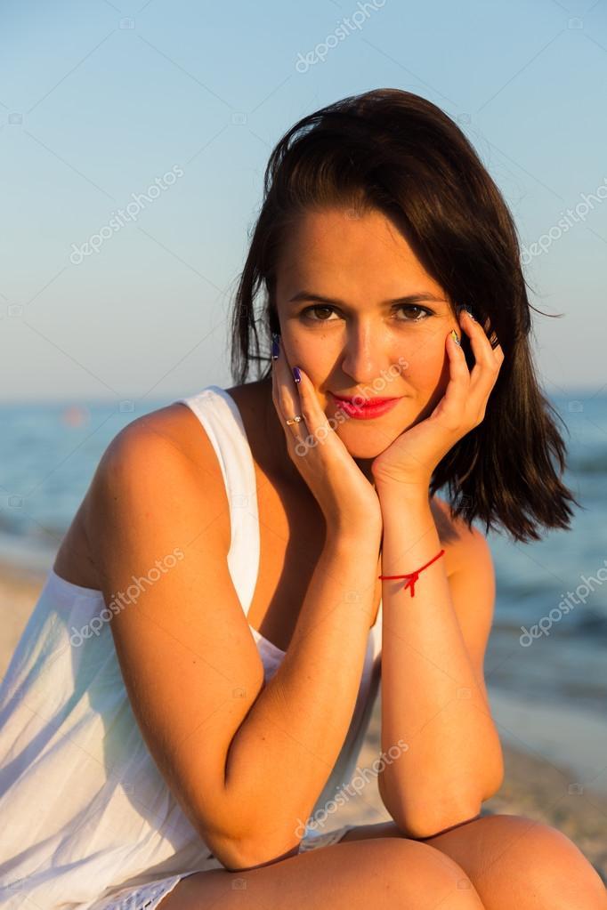81810298b280 Den unga vackra flickan i en vit klänning på stranden. Foto vacker flicka  på stranden. Flicka poserar i förföriska sätt. Foto för resor och sociala  ...