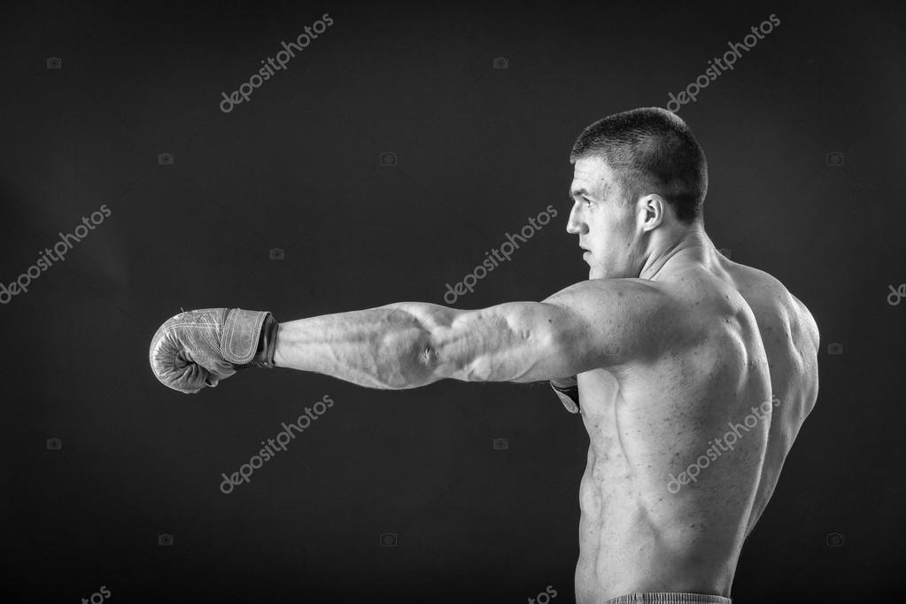 The man in boxing gloves  Young Boxer fighter over black
