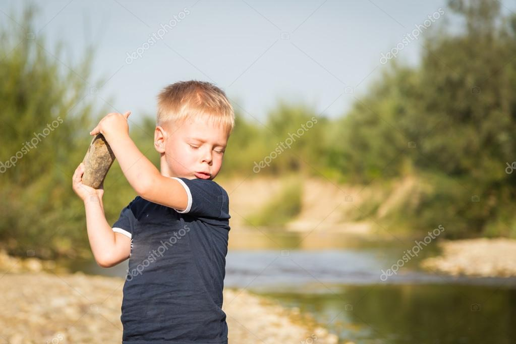 Boy throwing stones to the water