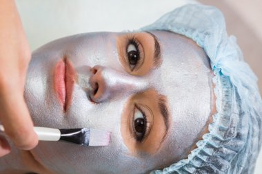 Therapist applying mask to face of woman