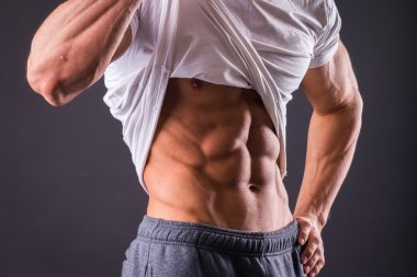 Man shows his abdominal muscles