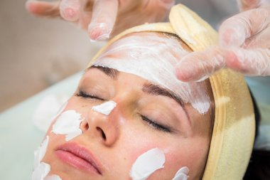 Young woman receiving facial mask