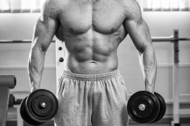 Man doing exercises with dumbbells in the gym