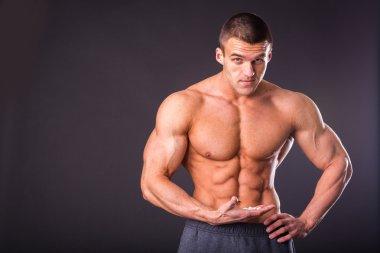 Muscular man holding a pill