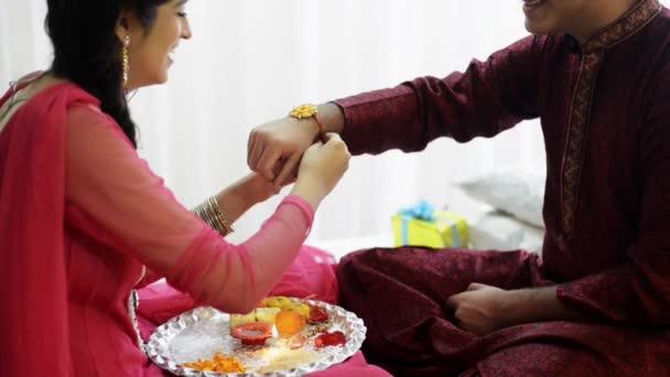 Girl tying rakhi to brother's wrist