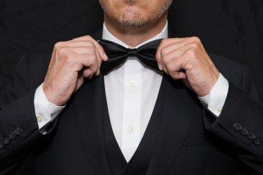 Gentleman in Black Tie Straightens His Bowtie