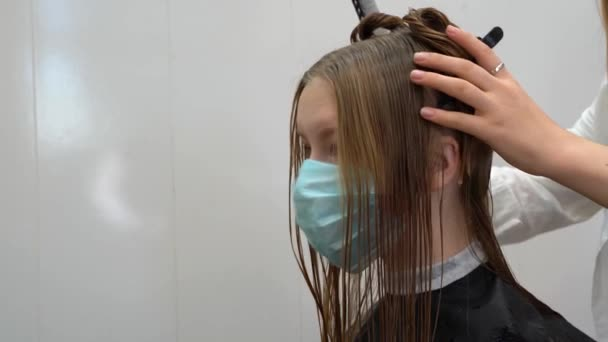 a girl wears medicine mask with wet hair gets a haircut in a barbershop