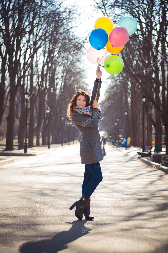 Beautiful woman with colorful balloons in the spring park