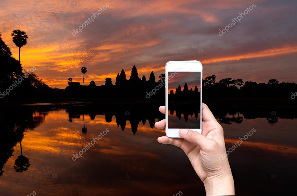 Female hands holding mobile smart phone taking pictures Silhouette of Angkor Wat sunrise at Siem Reap. Cambodia