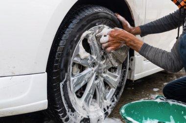 Worker washing car wheel
