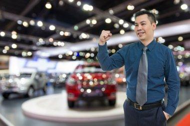 Happy car salesman on auto show