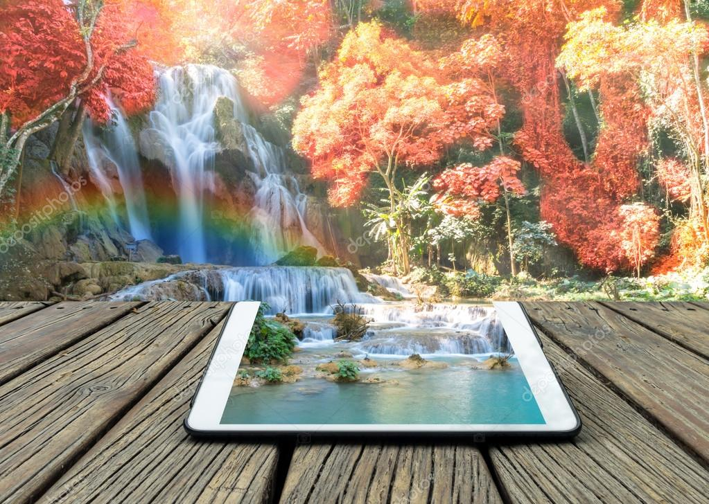 Conceptual image of tablet on Beautiful waterfall