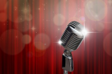 Retro microphone over red curtain