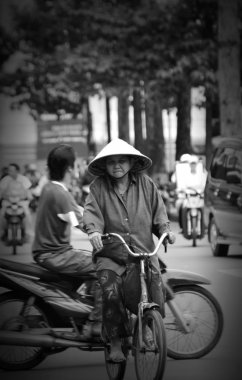 HOCHIMINH CITY, VIETNAM - NOV 03: An unidentified old woman is cycling in busy Hochiminh city traffic on November 03, 2007 in Hochiminh city, Vietnam
