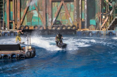 SINGAPORE - JULY 6: Undefined Stuntman in action riding the water scooter in the live stunt show called Waterworld on July 6,2012 at the Universal Studios Singapore.