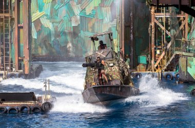SINGAPORE - JULY 6: Undefined Stuntman in action shooting the machine gun on the warship in the live stunt show called Waterworld on July 6,2012 at the Universal Studios Singapore.