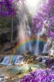 Schöner Wasserfall mit weicher Fokus und Regenbogen im Wald