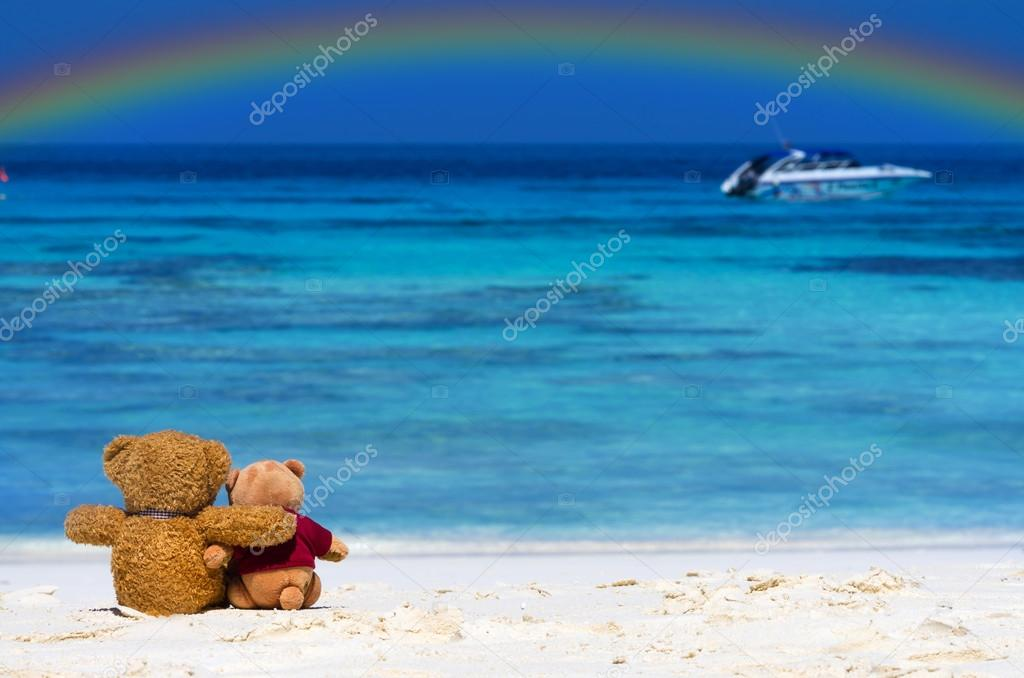 Two TEDDY BEAR brown color sitting on the beautiful beach with rainbow