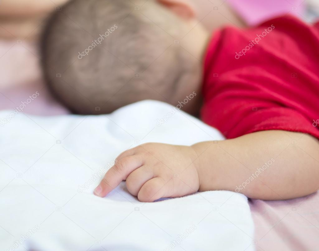 Asian baby sleeping on the bed with middle finger