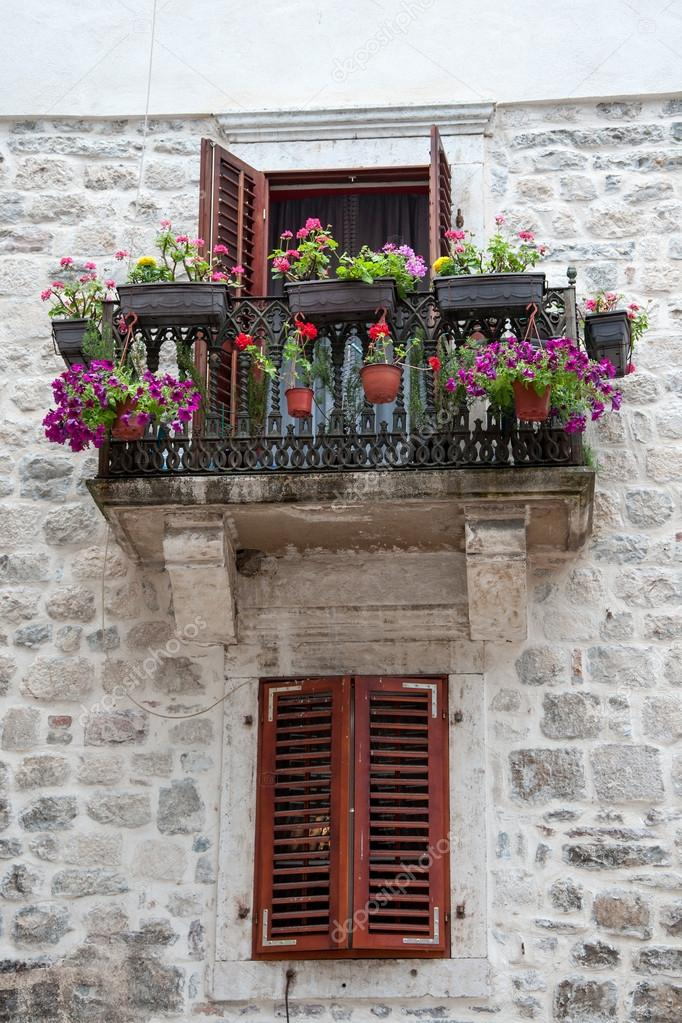 Vecchio balcone con fiori e finestra con persiane foto for Finestra con fiori disegno