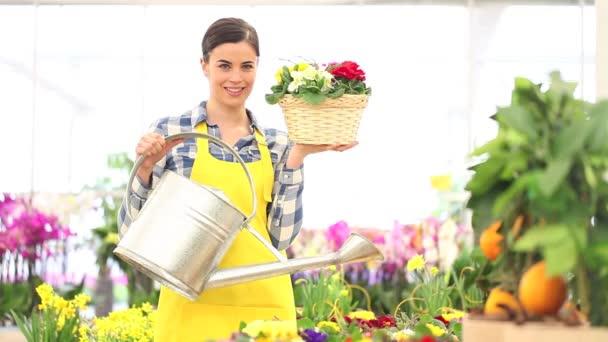 jarní koncepce, usmívající se žena květinářství s košíkem květin a konev