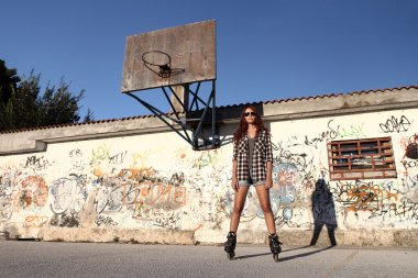 girl with roller skates on graffiti background and a basketball
