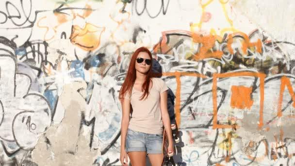 Mädchen mit Skateboard auf Hintergrund von Graffiti