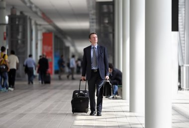 Businessman walking with trolley through the crowd on a business trip