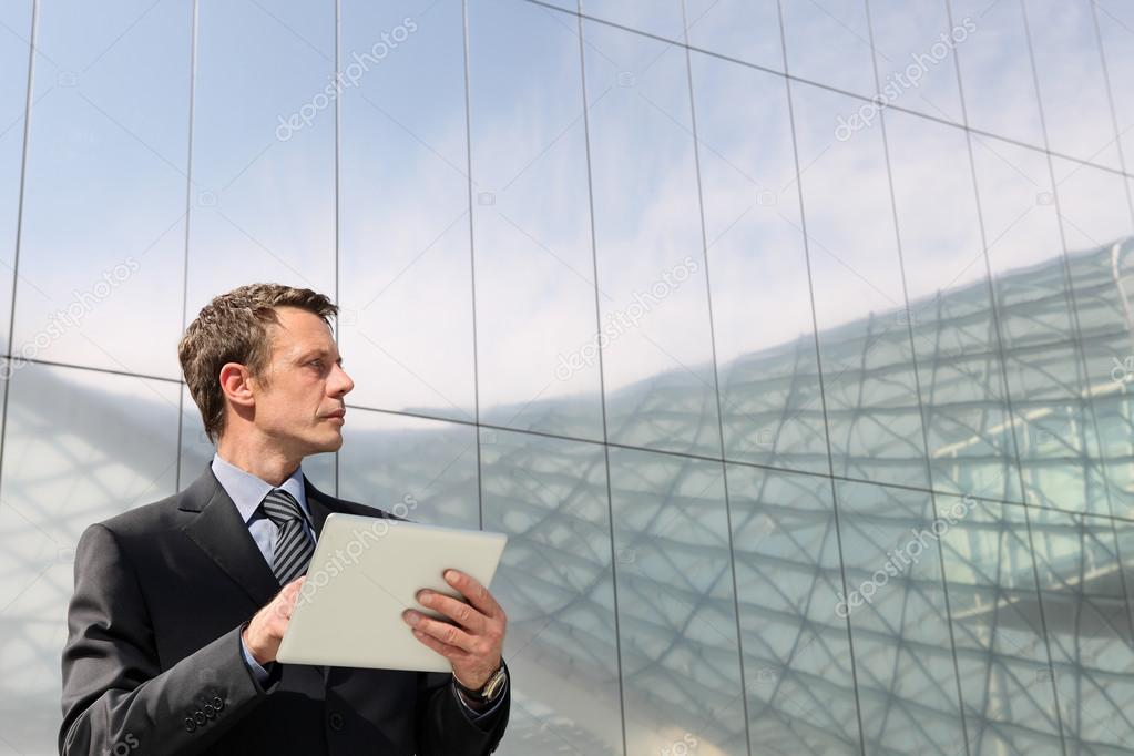 Businessman with tablet that looks far into the sky, in a scene of urban building with many glass windows
