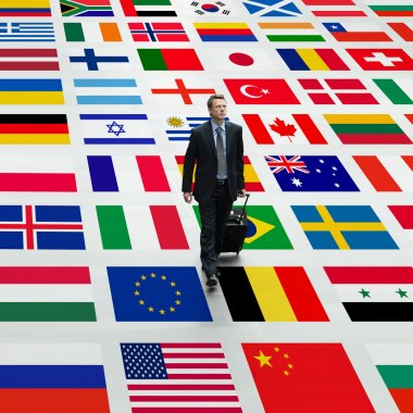 Business man travels the world, walking on a background of international flags