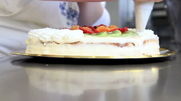 Pastry chef prepares fruit cake with whipped cream